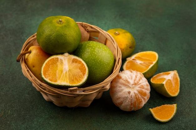 Vista superior de frutas frescas, como tangerinas, maçãs, peras, kiwi, em um balde com tangerinas cortadas pela metade isoladas