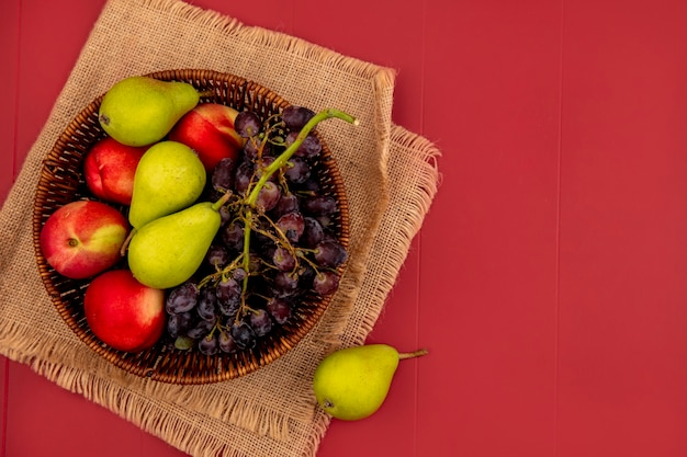 Vista superior de frutas frescas, como uva pêssego em uma tigela de madeira em um pano de saco sobre um fundo vermelho com espaço de cópia