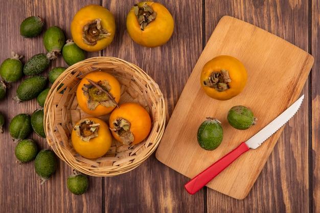 Vista superior de frutas frescas de caqui em um balde com feijoas e caqui em uma placa de cozinha de madeira com uma faca em uma superfície de madeira