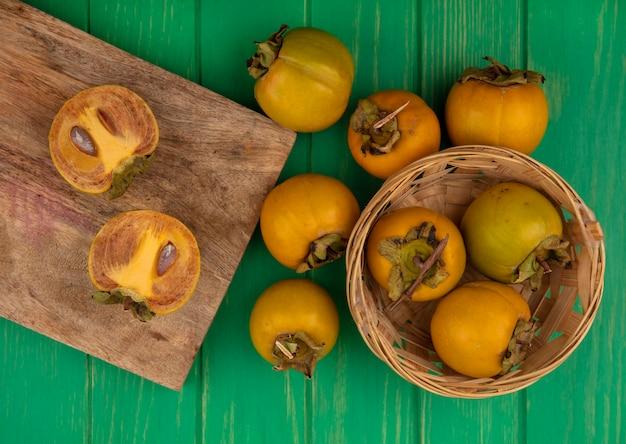 Vista superior de frutas frescas de caqui em uma placa de cozinha de madeira com frutas de caqui em um balde em uma mesa de madeira verde