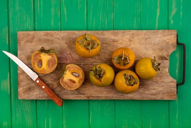 Vista superior de frutas frescas de caqui em uma placa de cozinha de madeira com uma faca em uma mesa de madeira verde