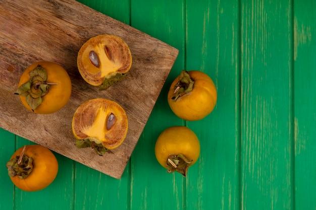 Vista superior de frutas frescas de caqui em uma placa de cozinha de madeira em uma mesa de madeira verde com espaço de cópia