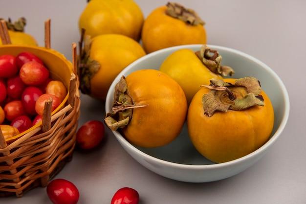 Vista superior de frutas frescas de caqui em uma tigela com frutas da cornalina em um balde em uma superfície cinza