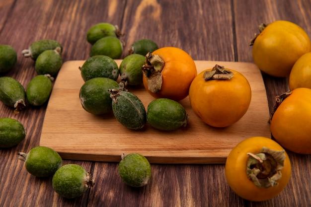 Vista superior de frutas frescas de caqui laranja com feijoas em uma placa de cozinha de madeira em uma superfície de madeira