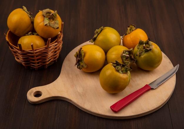 Vista superior de frutas frescas de caqui orgânico em uma placa de cozinha de madeira com uma faca em uma mesa de madeira