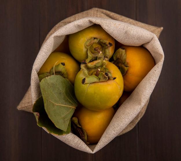 Vista superior de frutas frescas de caqui verde com folhas em um saco de estopa sobre uma mesa de madeira