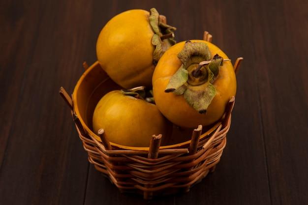 Vista superior de frutas frescas de caqui verdes em um balde sobre uma mesa de madeira
