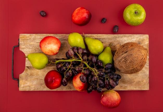 Vista superior de frutas frescas de verão, como videira, pêssego e coco em uma placa de cozinha de madeira sobre um fundo vermelho