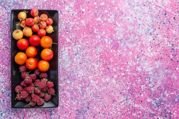 Vista superior de frutas frescas dentro de uma forma preta na superfície rosa
