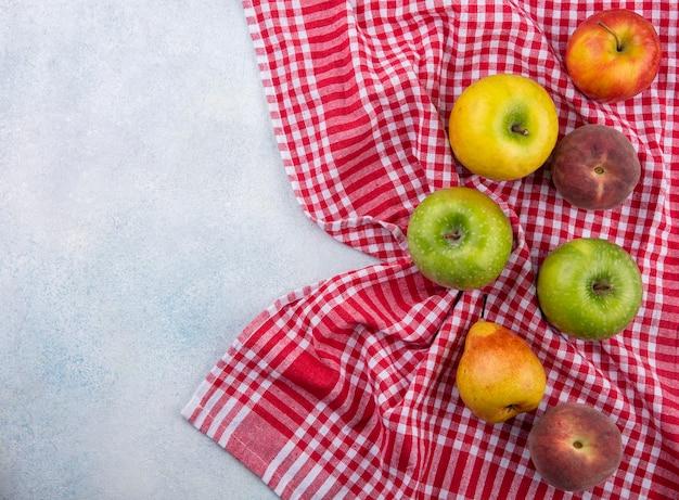 Vista superior de frutas frescas e coloridas, como maçã, pêra, pêssego, isolado na metade da toalha xadrez vermelha e branca com espaço de cópia