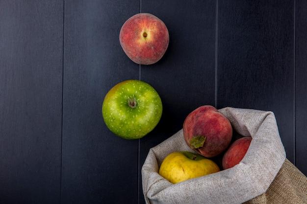 Vista superior de frutas frescas e coloridas, como pêssegos e maçãs em sacos de aniagem no preto