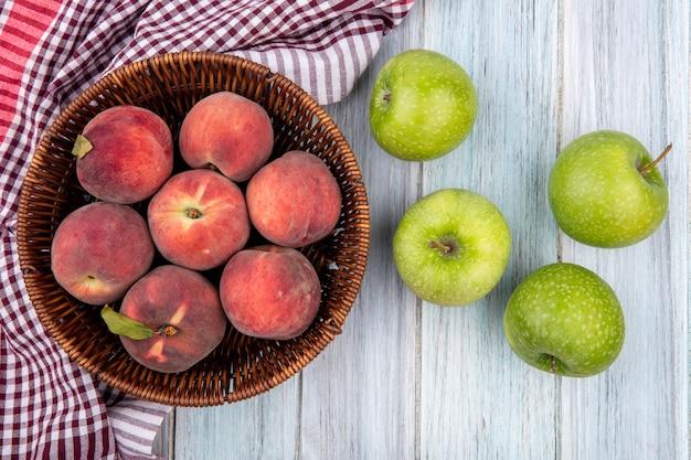 Vista superior de frutas frescas e coloridas, como pêssegos em um balde em uma toalha de mesa xadrez e maçãs verdes isoladas em madeira cinza