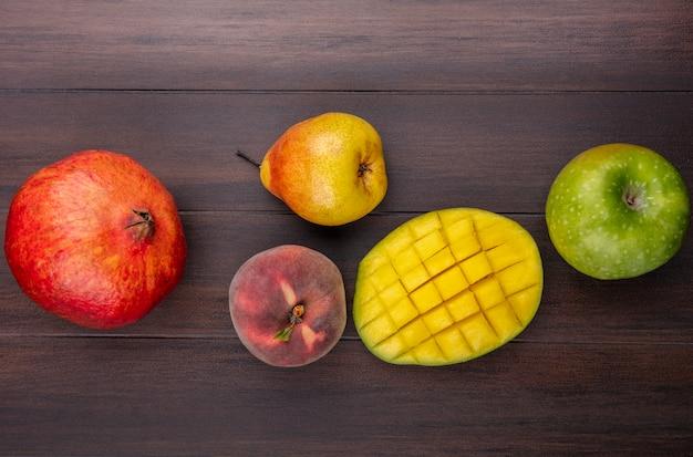 Vista superior de frutas frescas e coloridas, como romã fatiada, manga, pêra, maçã, pêssego, na madeira