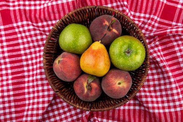 Vista superior de frutas frescas e deliciosas, como maçã, pêssego, pêra, no balde, em uma toalha xadrez vermelha e branca