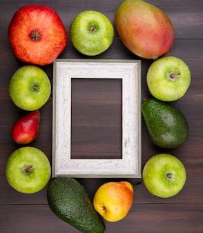 Vista superior de frutas frescas e deliciosas, como maçã, romã, pêra, madeira, com espaço de cópia
