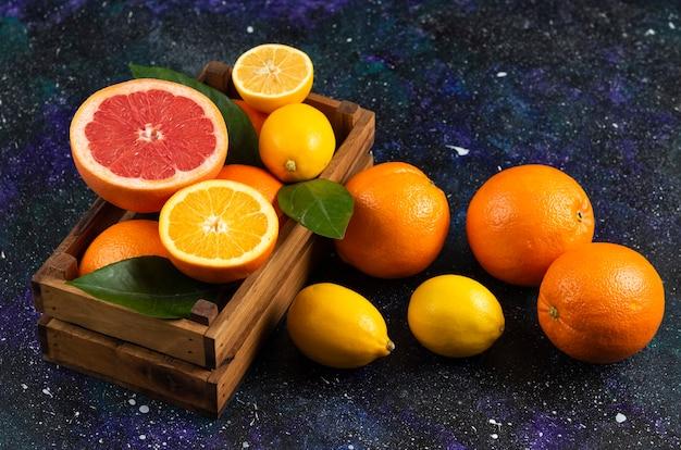 Vista superior de frutas frescas em uma cesta de madeira e no solo.