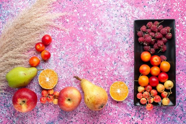 Vista superior de frutas frescas, framboesas e ameixas dentro de uma forma preta na superfície rosa