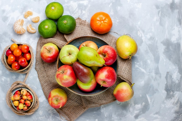 Vista superior de frutas frescas, maçãs e manga em uma superfície branca clara