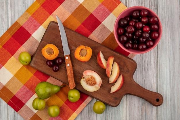 Vista superior de frutas inteiras cortadas e fatiadas como cereja de pêssego damasco com faca na tábua e cerejas em uma tigela com pêra e ameixas em pano xadrez em fundo de madeira