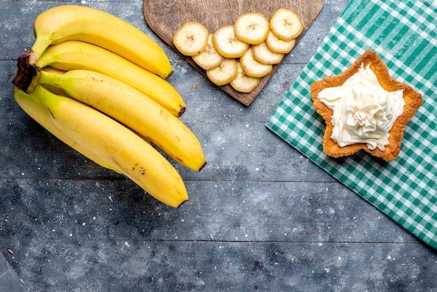 Vista superior de frutas inteiras de bananas frescas amarelas com bolo na mesa cinza, sabor de vitamina de frutas silvestres