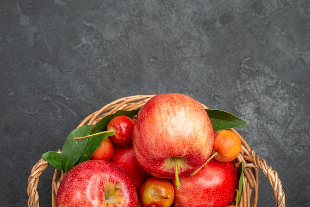 Vista superior de frutas, maçãs e cerejas na cesta na mesa escura