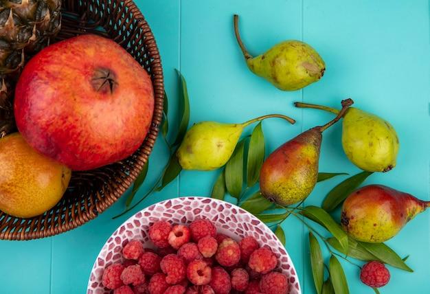 Vista superior de frutas na cesta e tigela de framboesa com pêssegos e folhas na superfície azul