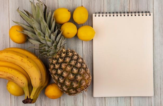 Vista superior de frutas ricas em vitaminas, como banana, abacaxi e limão, isoladas em um fundo cinza de madeira com espaço de cópia