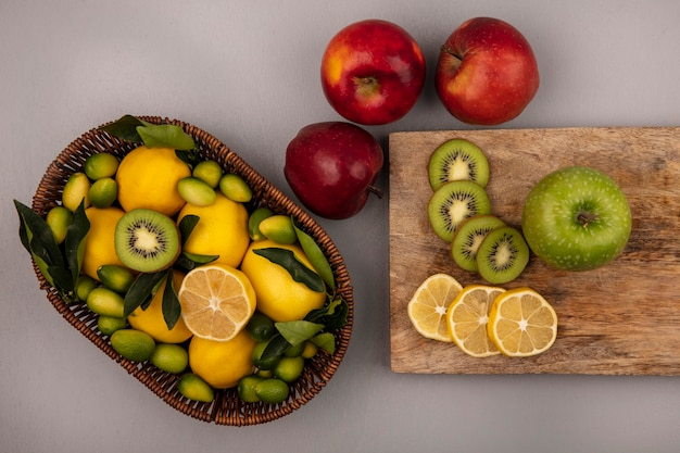Vista superior de frutas ricas em vitaminas, como kinkans de kiwi e limões em um balde com fatias de limão e kiwi em uma placa de cozinha de madeira com maçãs isoladas em um fundo cinza