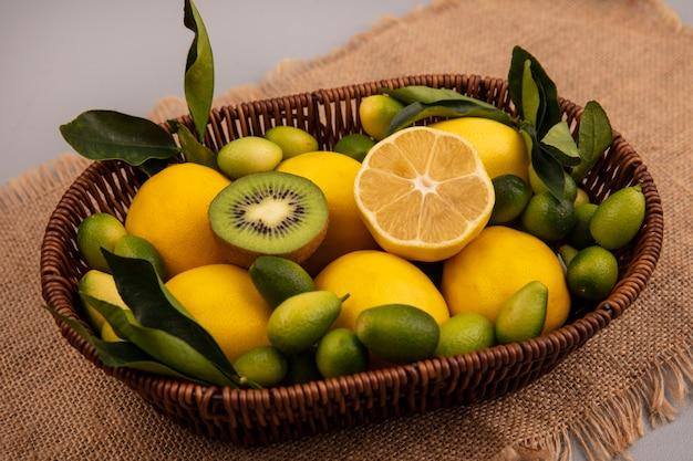 Vista superior de frutas saudáveis, como kinkans de kiwi e limões em um balde em um pano de saco em uma parede cinza
