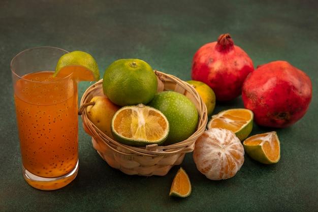 Vista superior de frutas saudáveis, como maçãs, pêra, kiwi, em um balde com suco fresco em um copo com tangerinas e romãs isoladas