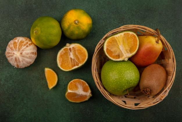 Vista superior de frutas saudáveis e frescas, como maçãs, pêra, kiwi, em um balde com tangerinas isoladas