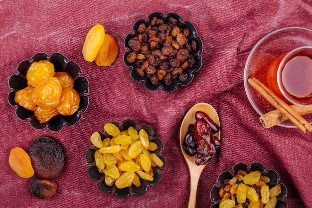 Vista superior de frutas secas, ameixas de cereja, passas, damascos e datas secas em latas de mini torta servidas com chá sobre fundo de cor vermelho escuro