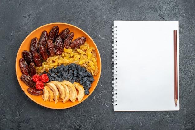 Vista superior de frutas secas com passas dentro do prato no espaço cinza