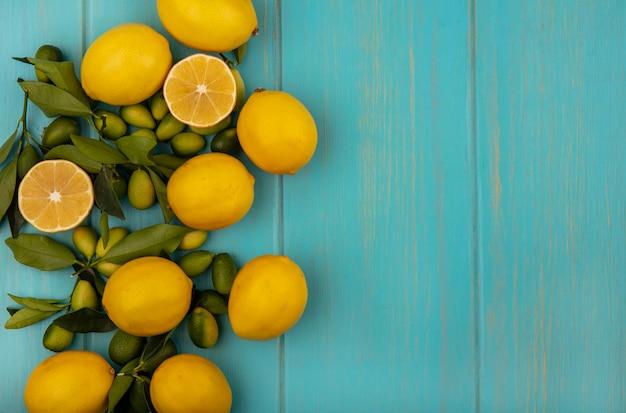 Vista superior de frutas verdes e amarelas, como kinkans e limões, isolados em uma parede de madeira azul com espaço de cópia