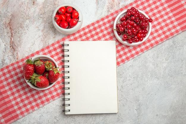 Vista superior de frutas vermelhas com bagas em um bloco de notas de frutas frescas de mesa branca