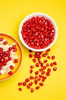 Vista superior de frutas vermelhas, duas tigelas de sementes de romã, frutas vermelhas e aveia