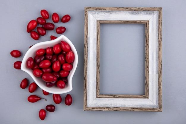 Vista superior de frutas vermelhas frescas em uma tigela branca em um fundo cinza com espaço de cópia