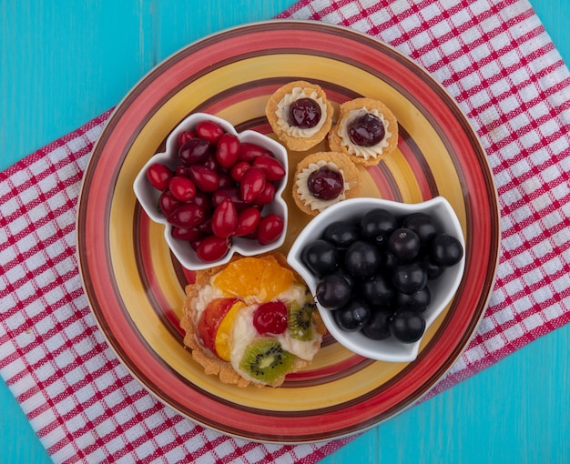 Vista superior de frutas vermelhas frescas em uma tigela com uvas e tortas em um pano xadrez vermelho sobre um fundo azul de madeira