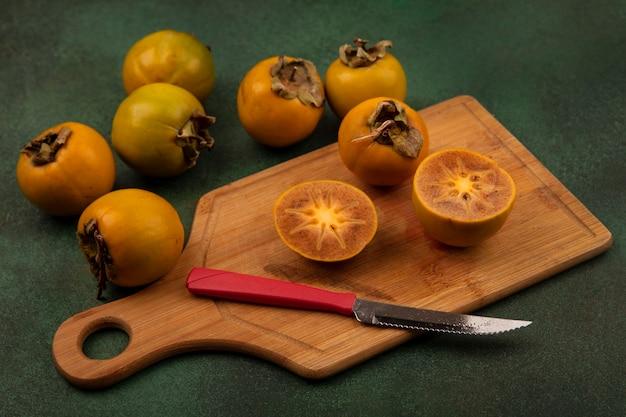 Vista superior de frutos de caqui cortados ao meio em uma placa de cozinha de madeira com uma faca com frutos de caqui inteiros isolados em uma superfície verde