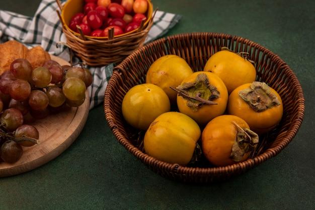 Vista superior de frutos de caqui em um balde com uvas em uma placa de cozinha de madeira em um pano xadrez sobre um fundo verde