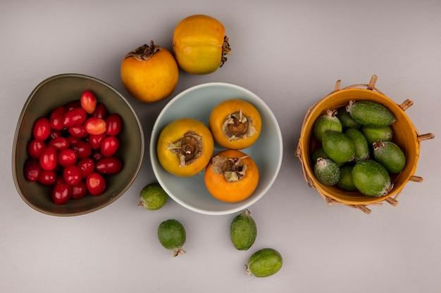 Vista superior de frutos de caqui laranja em uma tigela com feijoas em um balde e cerejas da cornalina em uma tigela em uma parede cinza