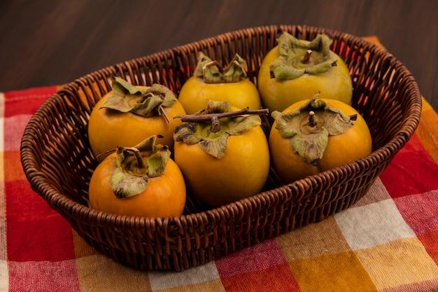 Vista superior de frutos de caqui orgânicos verdes em um balde em um pano xadrez sobre uma mesa de madeira