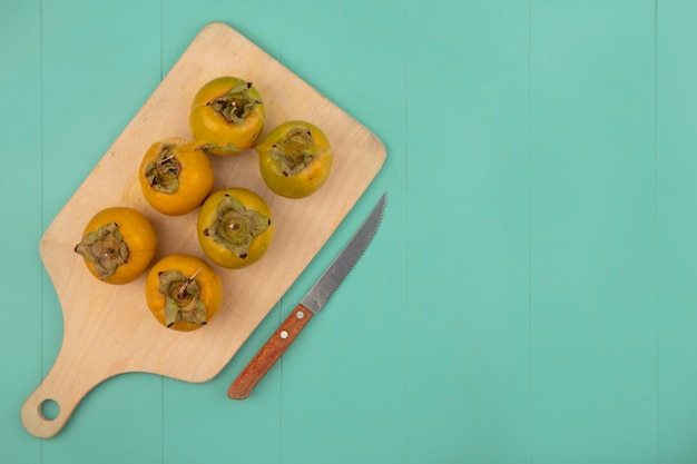 Vista superior de frutos de caqui verde laranja em uma placa de cozinha de madeira com uma faca em uma mesa de madeira azul com espaço de cópia
