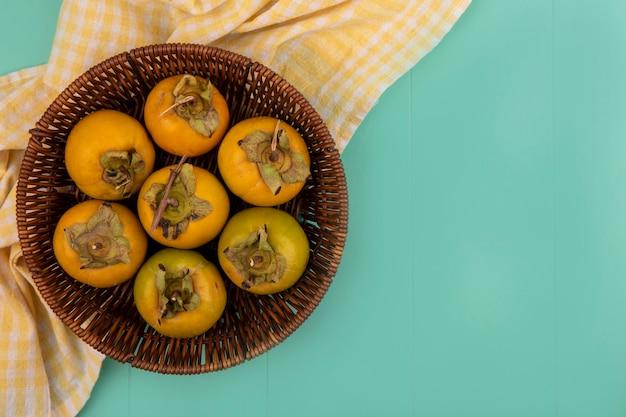 Vista superior de frutos de caqui verdes alaranjados em um balde em um pano xadrez amarelo