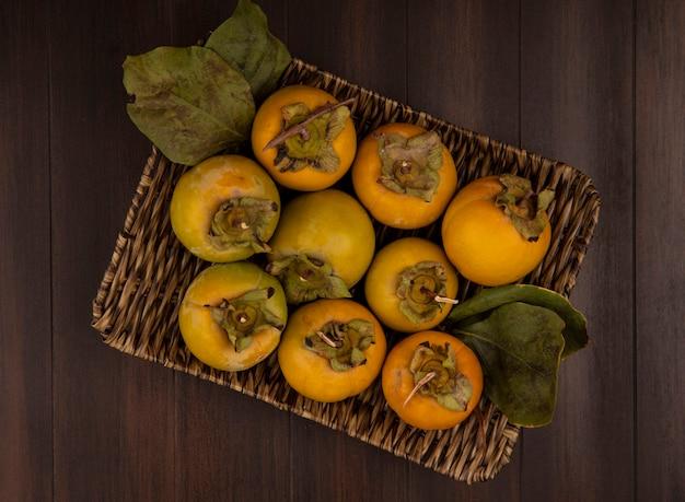 Vista superior de frutos de caqui verdes em uma bandeja de vime com folhas em uma mesa de madeira