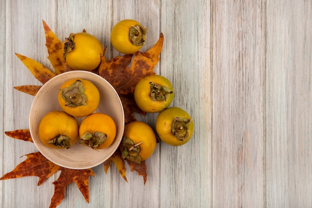 Vista superior de frutos de caqui verdes em uma tigela com folhas em uma mesa de madeira cinza com espaço de cópia