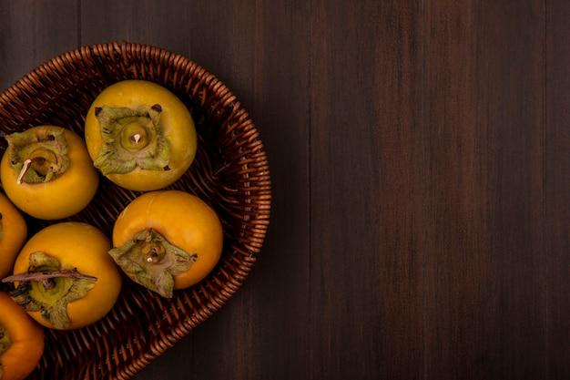 Vista superior de frutos verdes de caqui em um balde em uma mesa de madeira com espaço de cópia