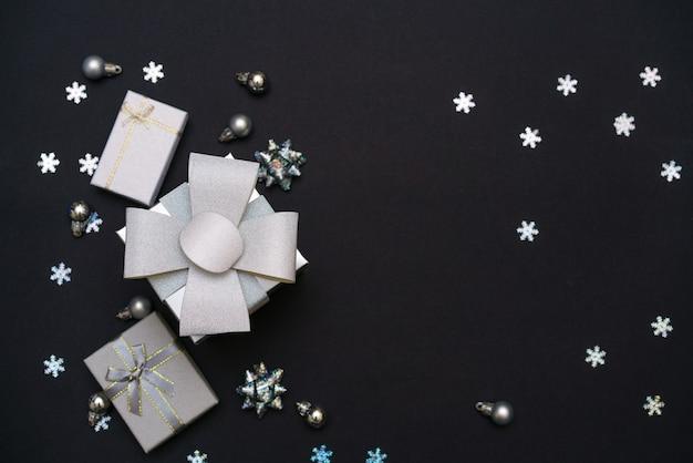 Vista superior de fundo escuro de natal preto com caixas de presente e brilhos com flocos de neve feliz natal.