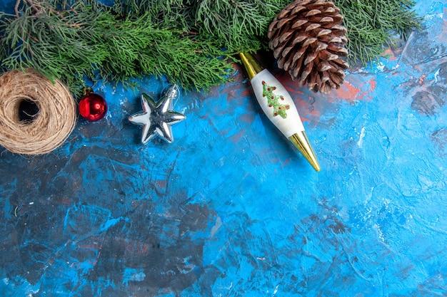 Vista superior de galhos de pinheiro com fio de palha de pinha na superfície azul-vermelha