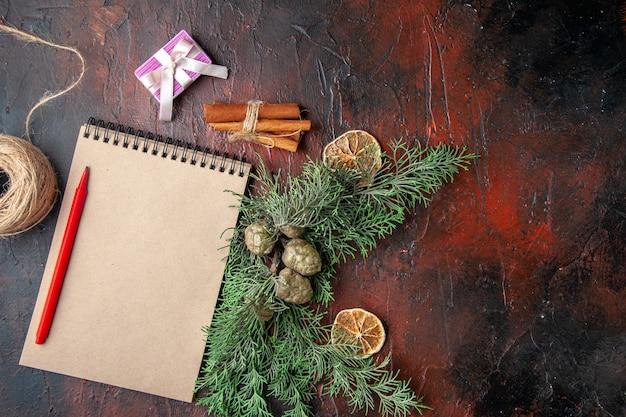 Vista superior de galhos de pinheiro e caderno espiral fechado com caneta de presente de limão e canela no lado direito em fundo escuro